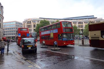 Regnerische Straßen von London, Großbritannien mit typischen roten Bussen und schwarzen Taxis