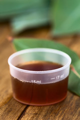 Eucalyptus cough syrup in medicine cup with fresh Eucalyptus leaves (Selective Focus, Focus on the 15ml sign on the cup)
