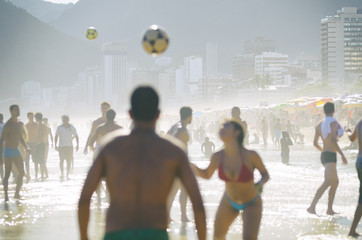 Brazilian men and women play keepy uppy on the shore of Ipanema Beach at Posto 9, a famous gathering place for the game, called altinho.