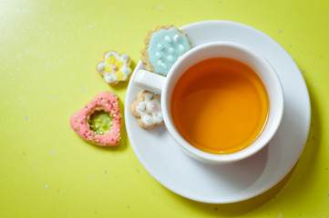 closeup of ginger cookies and cup of tea on light green