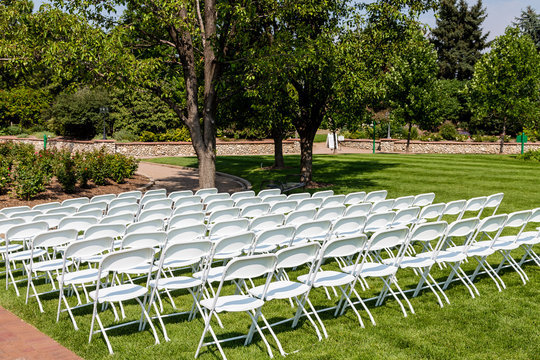 White Folding Chairs on Green Lawn