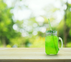 Jar with green ice drink and straw on wooden table over green bo