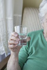 wrinkled hand of a senior person holding a glass of water