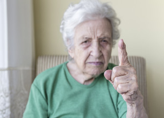 an angry old woman with her finger up for admonition /warning