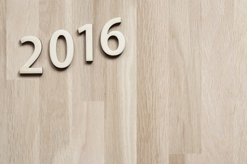 number 2016 on brown wooden background (new year 2015-2016)
