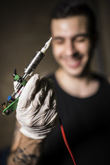 Man with tattoo machine in hand, blurred face.