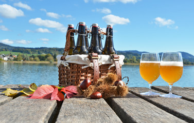 Beer on the wooden jetty against a lake