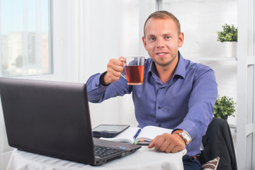Businessman working in office, sitting at a table holding cup and looking straight