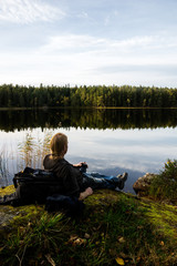hiker taking a rest and have a cup of coffe by a lake