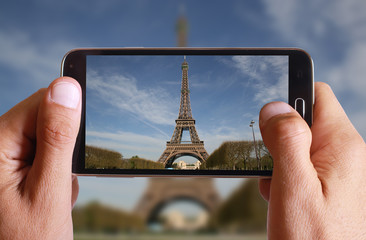 Male hand taking photo of Eiffel tower in Paris with cell, mobile phone. French holiday.