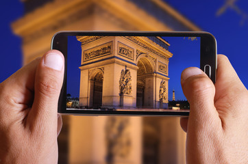 Male hand taking photo of triunfal arc in Paris with cell, mobile phone. French holiday.