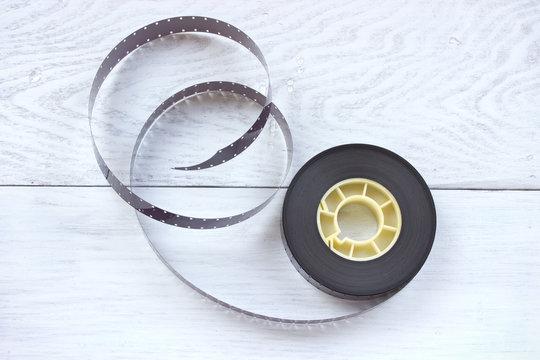 16mm film reel on white wooden background