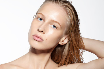 Fashion portrait of a blonde girl with wet hair and perfect skin