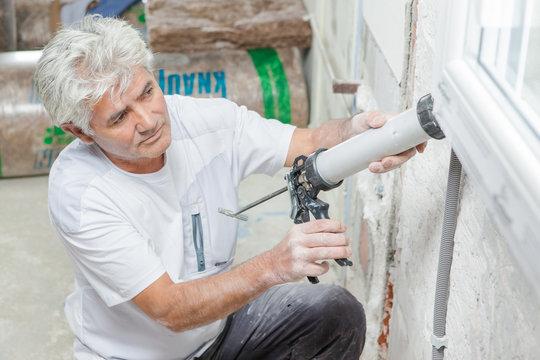 Handyman caulking a window frame
