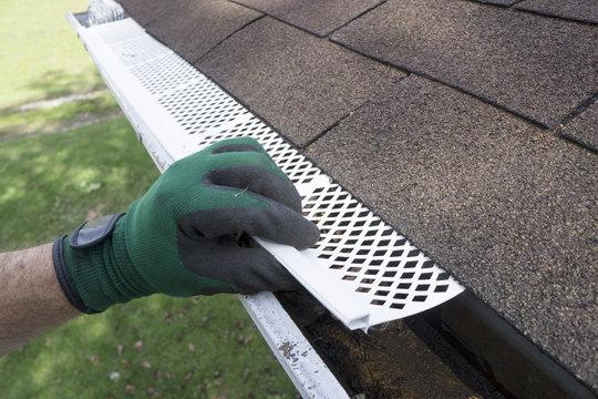 Contractor Adjusting Plastic Gutter Guards