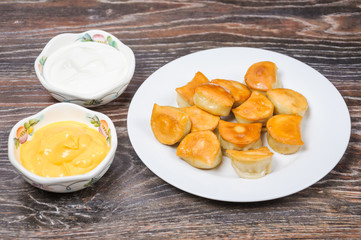 Fried dumplings, sour cream and cheese sauce