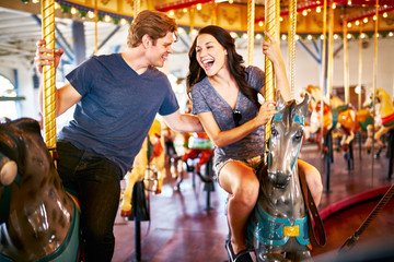 romantic couple riding carousel together on date with blurred motion