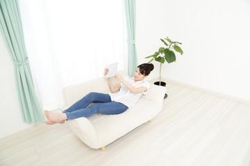 ソファーでタブレットを使っている女