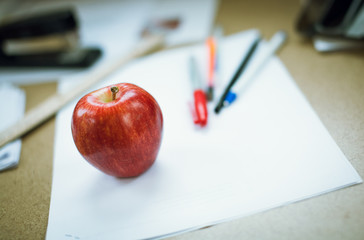 Apple on a white paper with pens. Back to school concept