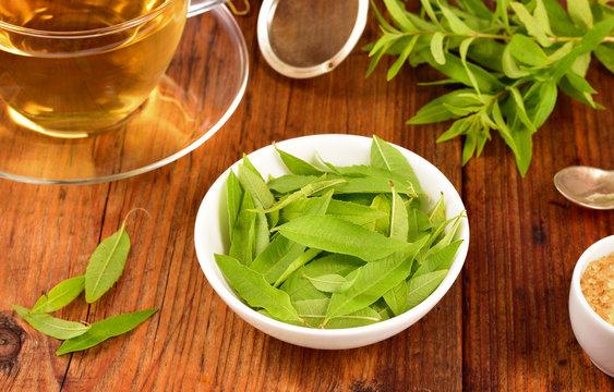 Lemon verbena leaves and tea on table.