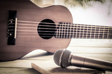 Microphone and acoustic guitar on wooden table in vintage color