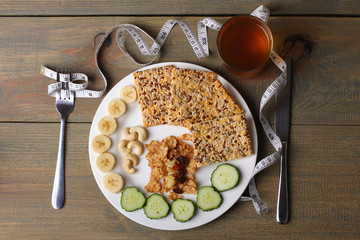 cookies, bananas, nuts and cucumbers, a measuring tape and Apple juice with utensils on wooden background
