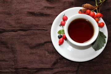 Autumn cup of tea with different berries