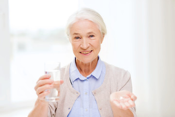 happy senior woman with water and medicine at home