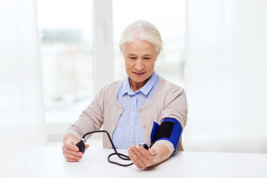 old woman with tonometer checking blood pressure