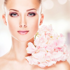 Pretty woman with a flowers at face