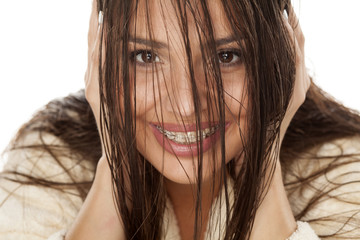 young beautiful woman in a bathrobe looking through her wet hair