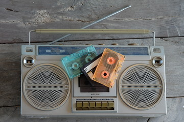Retro cassette tape recorder and tape cassette player and tape cassettes on wooden background