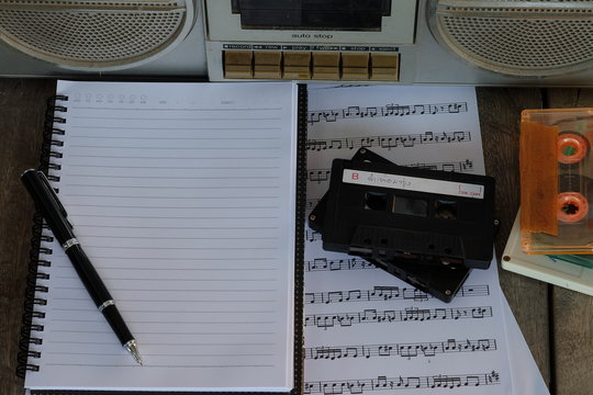 concept song composer: old tape cassette, song notes, cassette, notebook and pen on wooden background