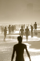 Silhouettes of beachgoers fill the shore of Ipanema at sunset on a summer afternoon in Rio de Janeiro, Brazil