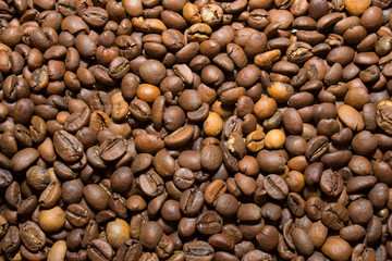 A scattering of coffee beans, close up.