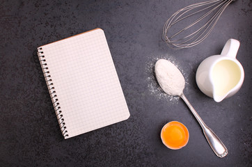 Baking ingredients, flour, egg, milk, and whisk. notebook