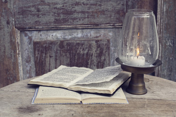 Open books and candlestick on a vintage wooden table