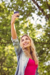 Low angle view of smiling woman taking selfie