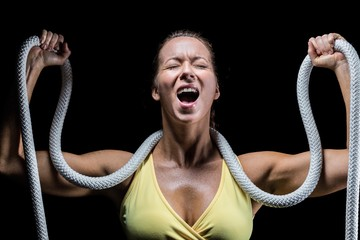 Angry woman holding rope around neck with arms raised