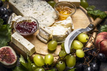 cheese plate with Gorgonzola and Camembert cheese knife honey jam light and dark grapes on a wooden cutting board close up