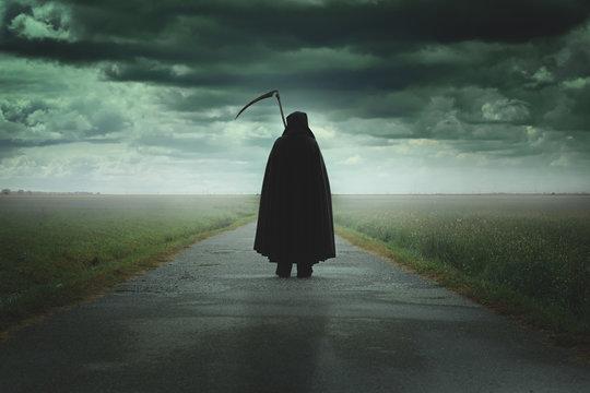 Grim reaper walking a desolate road