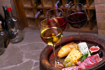 Red, rose and white  glasses and bottles of wine. Cheese, fig, grape, prosciutto and bread on old wooden barrel