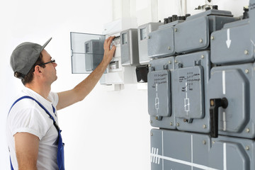 Korki, elektryk przełącza korki na tablicy rozdzielczej