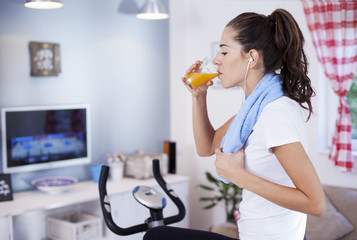 Lovely woman drinking orange juice while training on an exercise bike in her living room at home