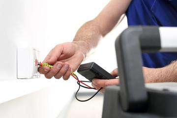 Podłączanie internetu. Mężczyzna montuje w ścianie gniazdko elektryczne, przyłącze internetu