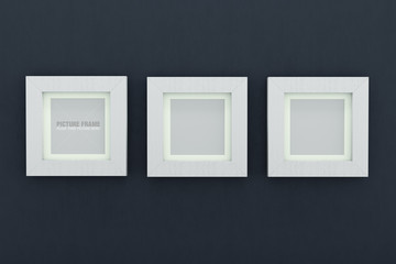 Square white wooden picture frames over navy blue wall