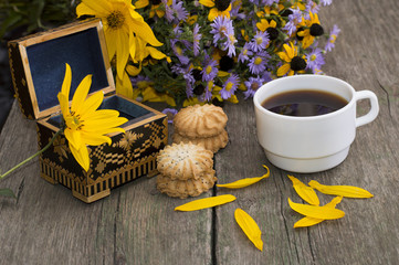 open casket, coffee, cookies, petals and wild flowers on an old