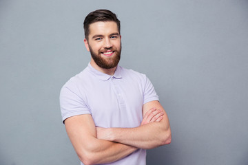 Happy man standing with arms folded