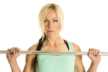 woman green tank top and barbell close by chest
