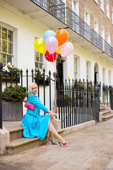 young woman sitting on a doorstep with party balloons